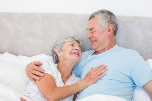 Loving senior man looking at wife in bed at home