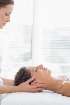 Therapist massaging woman in health spa