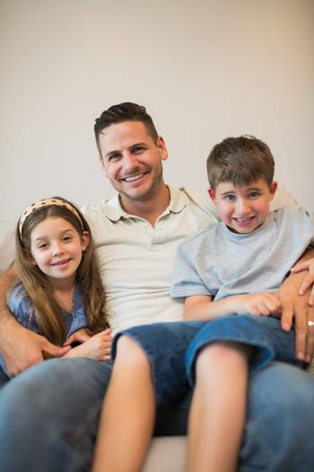 Portrait of father with son and daughter smiling while sitting on sofa