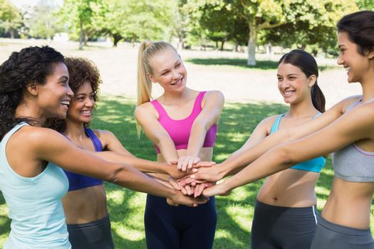 Fit young female friends stacking hands in the park
