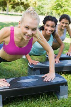 Smiling women doing step aerobics