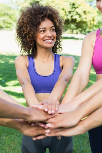 Happy young sporty woman stacking hands with friends in park