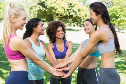 Group of female friends with hands stacked together in the park