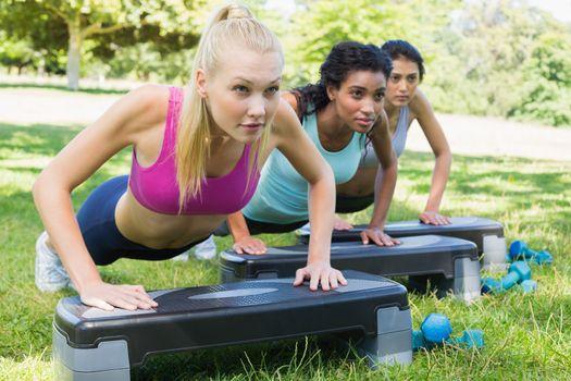 Determined women doing step aerobics