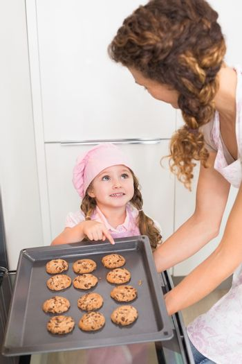 Mother taking cookies out of the oven with daughter pointing at one