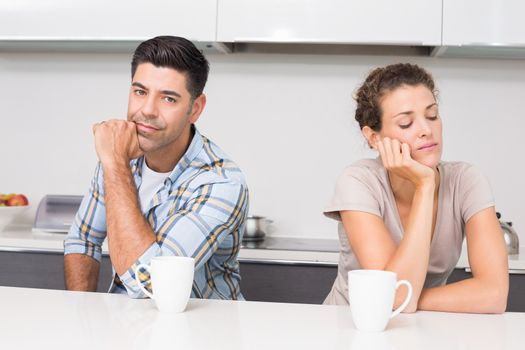 Troubled couple having coffee not talking to each other