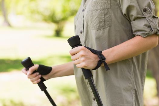 Mid section of a woman Nordic walking in park