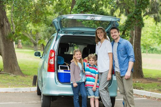 Portrait of a happy family of four by car trunk while on picnic