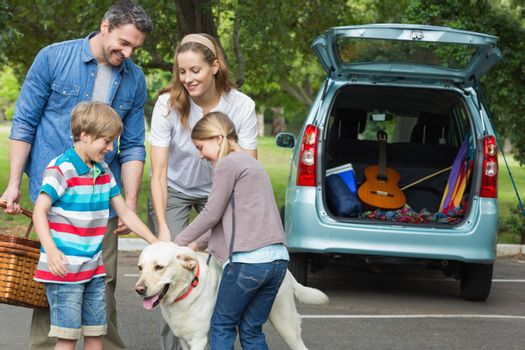 Portrait of a happy family of four with pet dog at picnic