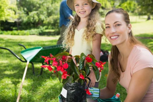 Portrait of a smiling mother and daughter engaged in gardening