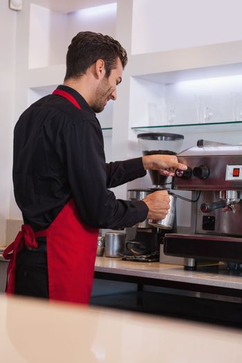 Smiling young barista steaming jug of milk