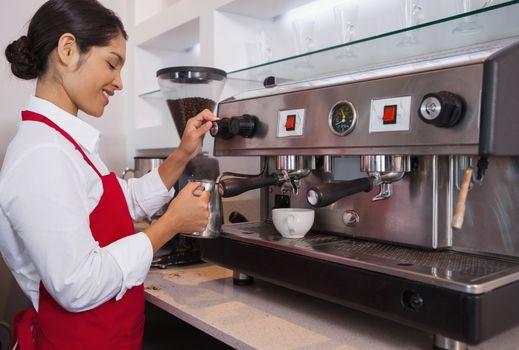 Pretty barista steaming jug of milk at coffee machine