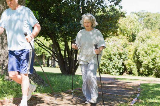 Mature couple Nordic walking at park