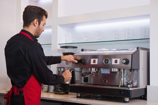 Handsome young barista steaming jug of milk