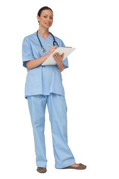 Smiling nurse in scrubs writing on clipboard