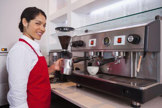 Pretty barista steaming jug of milk smiling at camera
