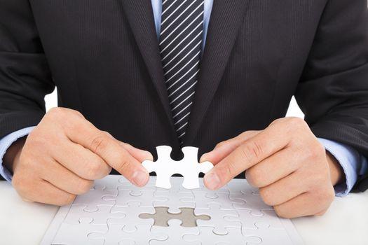 businessman holding a jigsaw