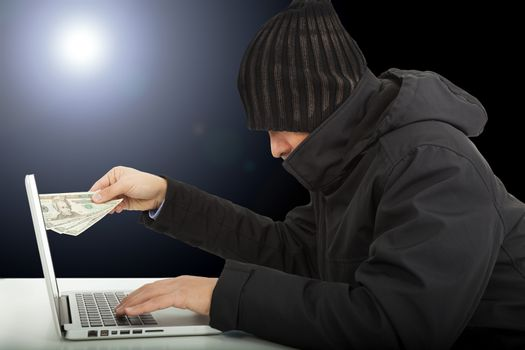 Computer hacker stealing money  in the darkness