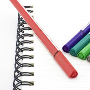 colorful pen with notebook isolated on white