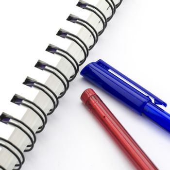 red and blue pen with notebook isolated on white