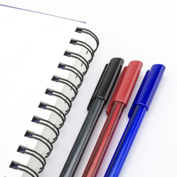 black red and blue pen with notebook isolated on white