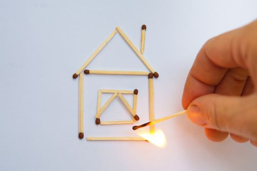burning match near model of the house