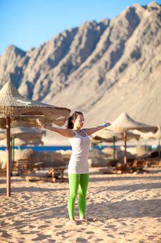 girl meditating on the beach