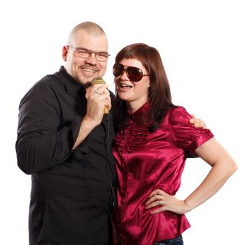 smiling couple sings into a microphone on a white background