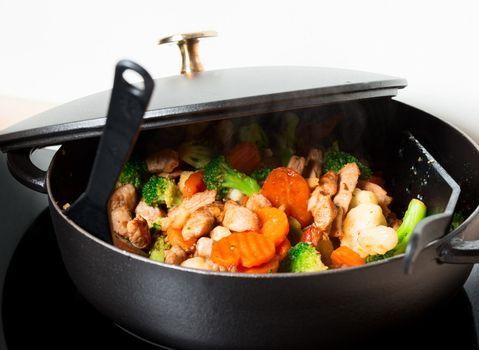 Frying meet and vegies in skillet steaming