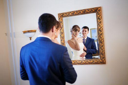 bride and groom by the mirrir