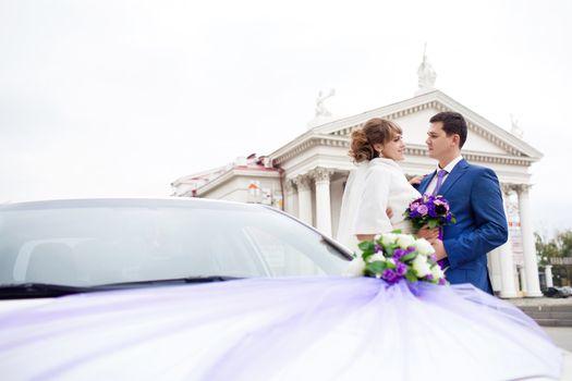 bride and groom near the car
