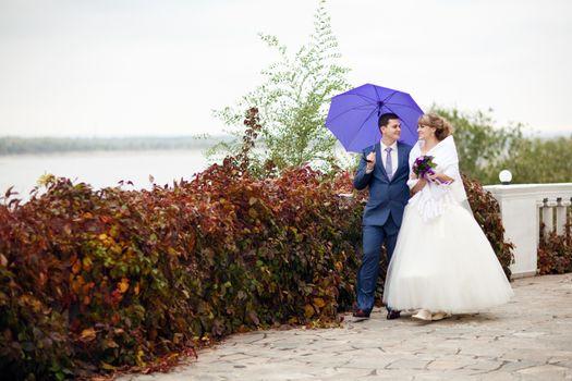 bride and groom walking under umbrella