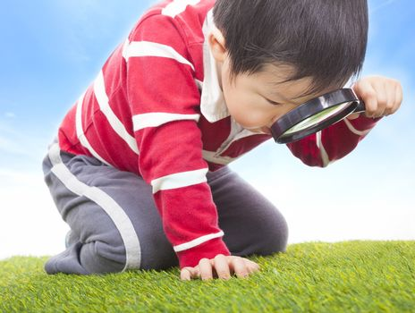 a boy exploring nature with magnifying glass