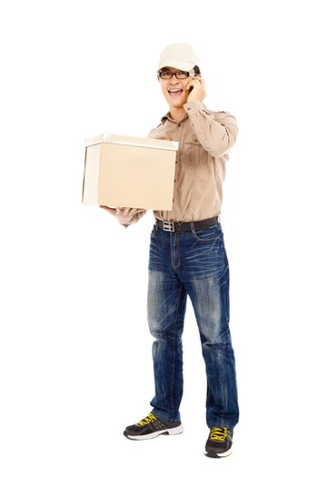 delivery man talking with cell phone and holding parcel