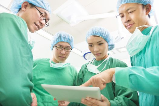 The surgeons useing  tablet  to discuss operating procedure
