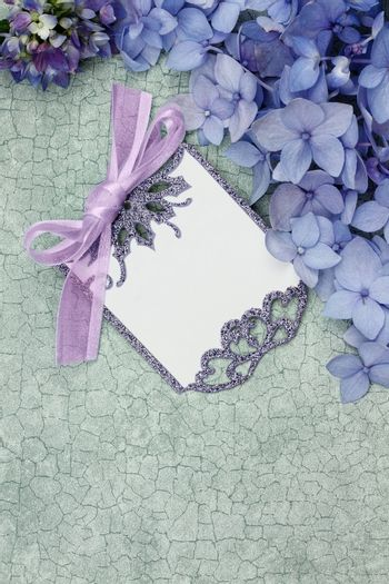 Blank card and flowers over green craquelure background with room for your text.