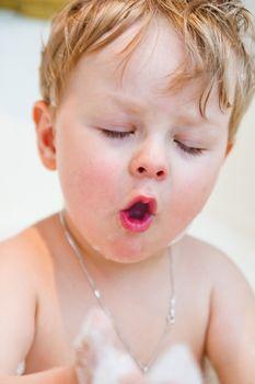 The little boy bathes in bathing with foam
