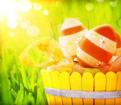 Easter eggs in the basket on fresh green grass, bright yellow sun light, eggs painted with red colours and floral ornament, religious holiday concept