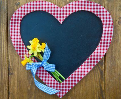 Heart-shaped chalkboard and fresh daffodils