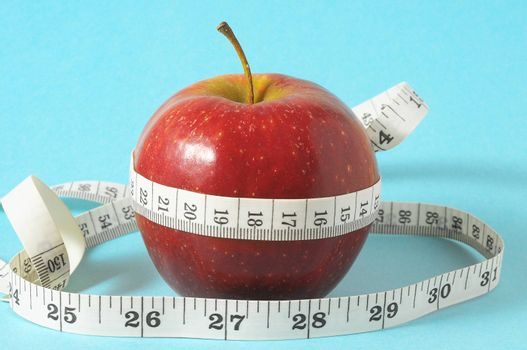 Measuring Tape Wrapped Around Red Apple as a Symbol of Diet