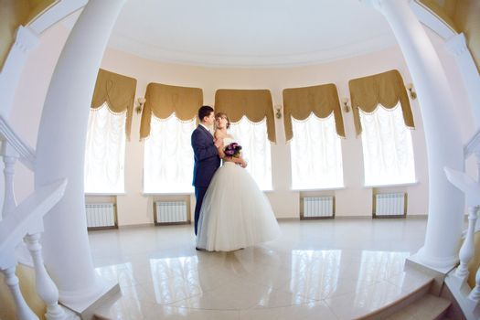 groom and bride in hall with staircase
