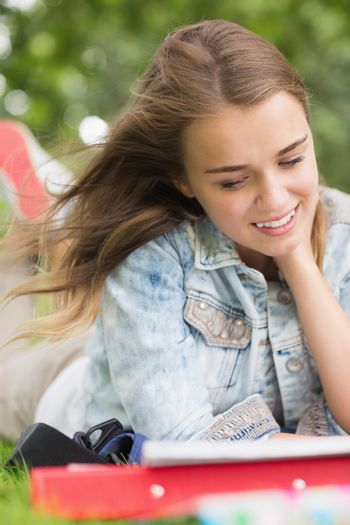 Smiling young student studying on grass
