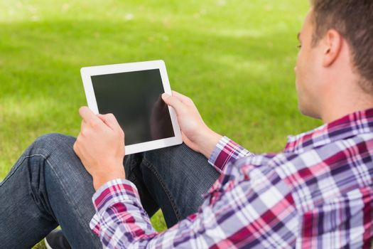 Happy student using his tablet outside