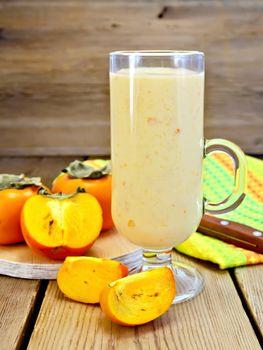 Milkshake with persimmons in goblet on board