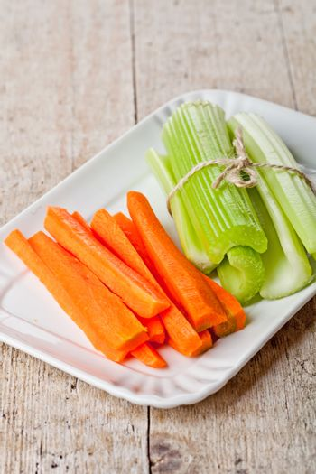 bundle of fresh green celery stems and carrot