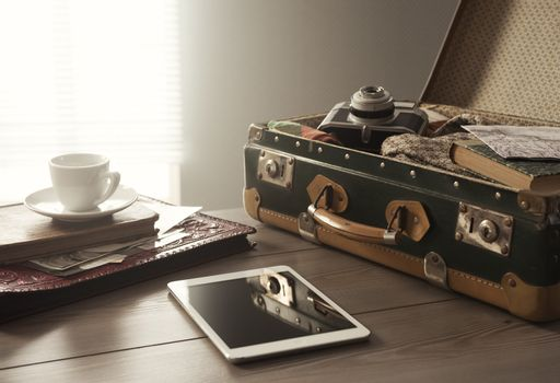 Traveler's suitcase with vintage items, tablet and a cup of coffee.