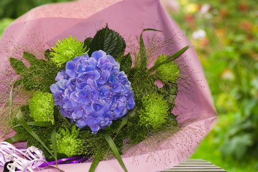 Blue and green bouquet of flowers wrapped in paper