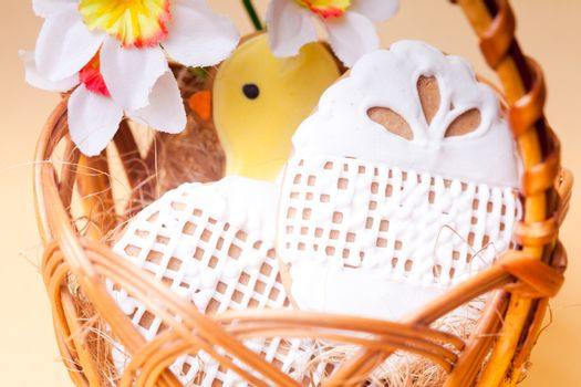 Easter cookies in basket over yellow background. Easter decor