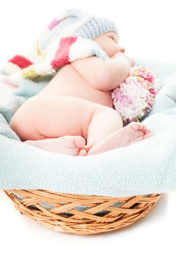 Newborn baby boy in the crochet hat lay in basket, focus on the feet