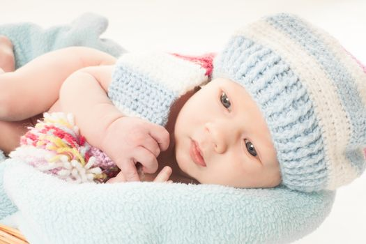 Newborn baby boy in the crochet hat lay in basket